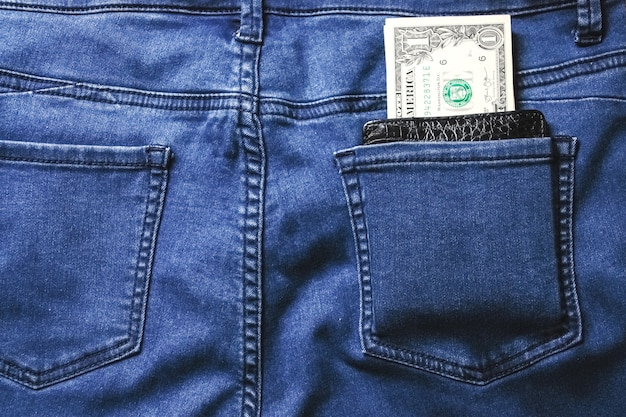 Черный кожаный кошелек с деньгами в задней части синего кармана джинсов джинсовой текстуры.