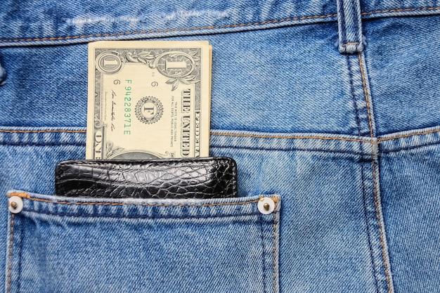 Черный кожаный кошелек с деньгами в заднем кармане джинсов из синего денима.