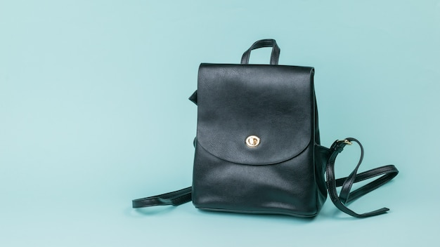 Black leather women's backpack on blue
