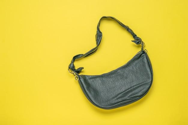 Черная кожаная женская сумка-банан на желтом фоне. вид сверху. плоская планировка.