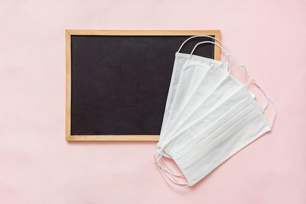ピンクの外科用医療用フェイスマスク付きテキストノート用の黒いレターボード