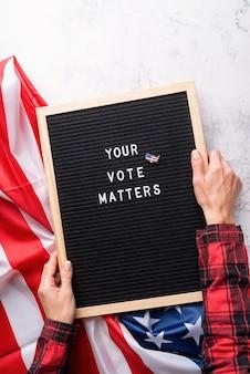 흰색 대리석 배경에 미국 국기와 함께 귀하의 투표가 중요한 텍스트가있는 블랙 레터 보드