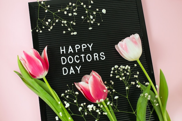 Black letterboard with white plastic letters with quote happy doctor's day and bunch of pink tulips on pink desk.