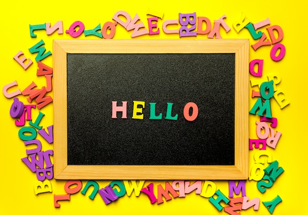 Black letterboard with wooden letters on yellow background