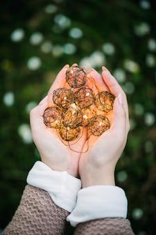 女性の手のひらに黒い照明付きのボール飾り