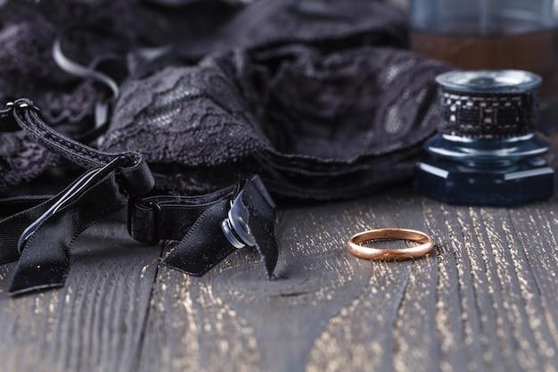 Black lingerie set, stockings, lace up corset choker on table