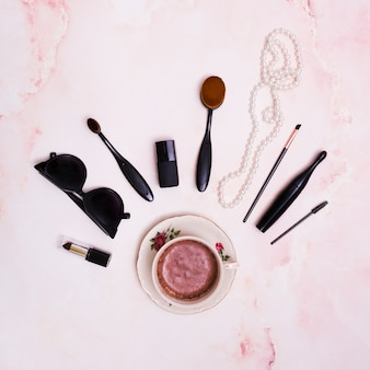 Black lipstick; sunglasses; makeup brush; mascara; white pearl necklace and nail varnish bottle over the ceramic coffee cup