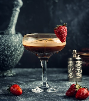 Black liquor with strawberries on the table