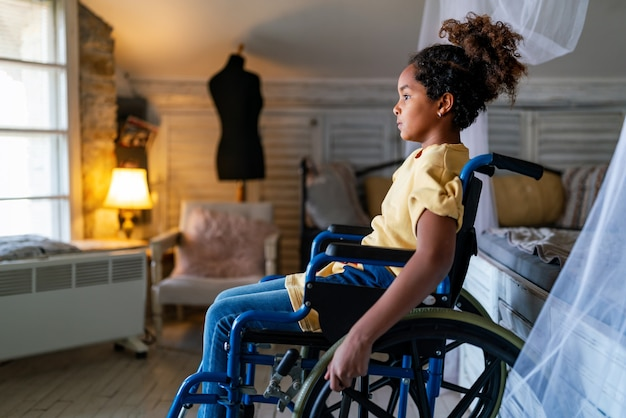Black little girl with disability in wheelchair at home. child, handicapped concept