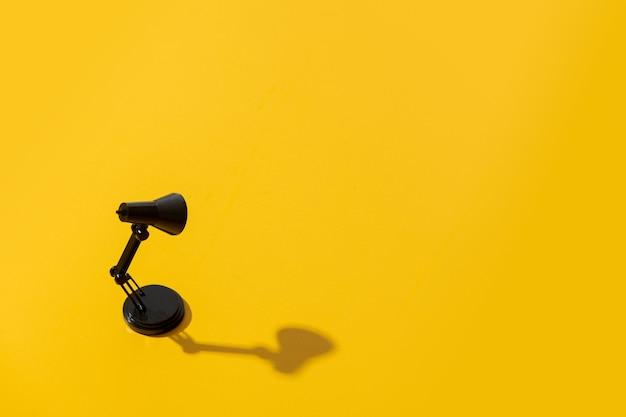Черная маленькая лампа на желтой поверхности