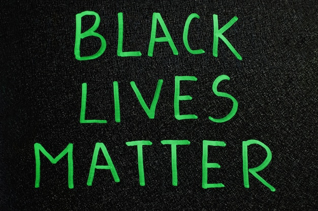 Black lives matter inscription in green words on board