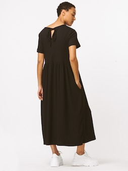 黒の長い形のないドレス、長袖、黒のハイシューズ。スリムなボディ、シルクの肌。白い笑顔、甘い顔、ブルネットの髪型。