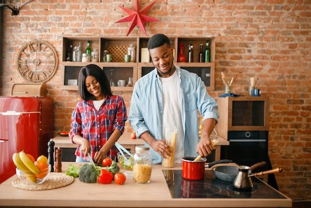 Черная любовь пара готовит романтический ужин