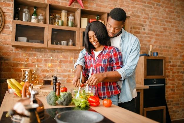 Черная влюбленная пара вместе готовит на кухне.