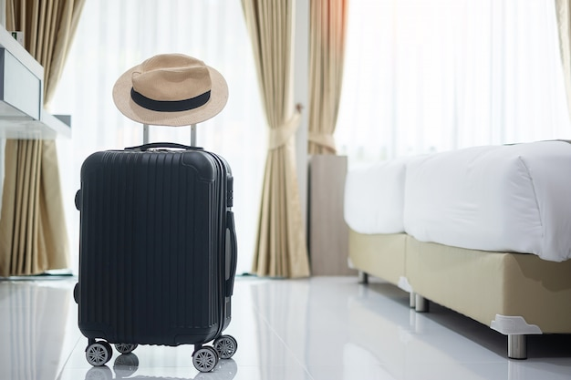 Black luggage and hat in modern hotel room with windows, curtains and bed. time to travel, relaxation, journey, trip and vacation concepts