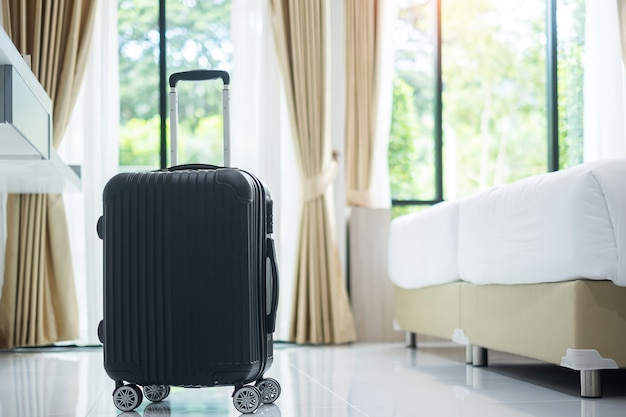 Black luggage in modern hotel room with windows. time to travel, relaxation, journey, trip and vacation concepts