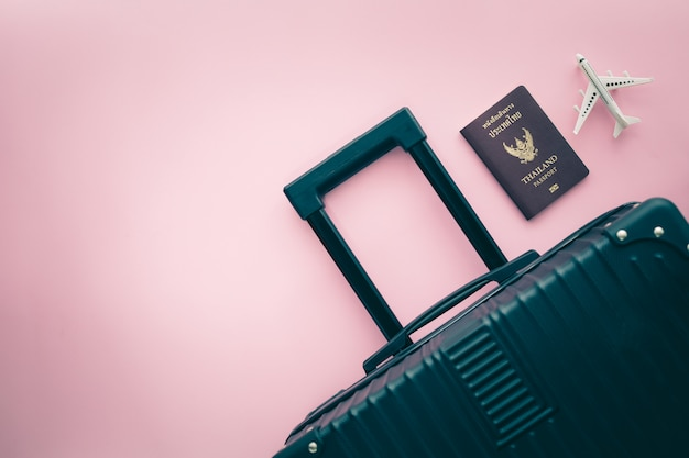 Black luggage, thai passport and white airplane model on pink background for travel and journey concept