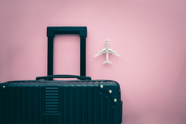 Black luggage and white airplane model on pink background for travel and journey concept