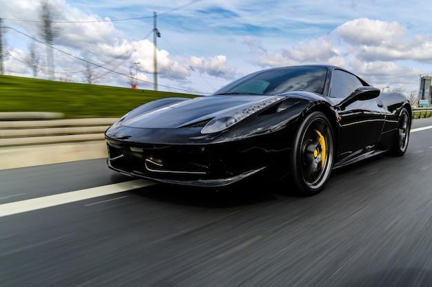 Черный роскошный седан на дороге.