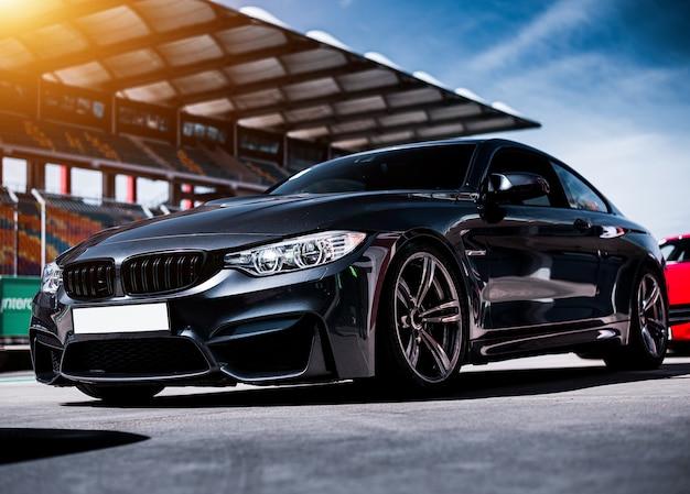 Черный роскошный спортивный седан, стоящий на трассе