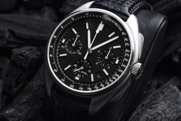 Черные роскошные часы на фоне черных углей