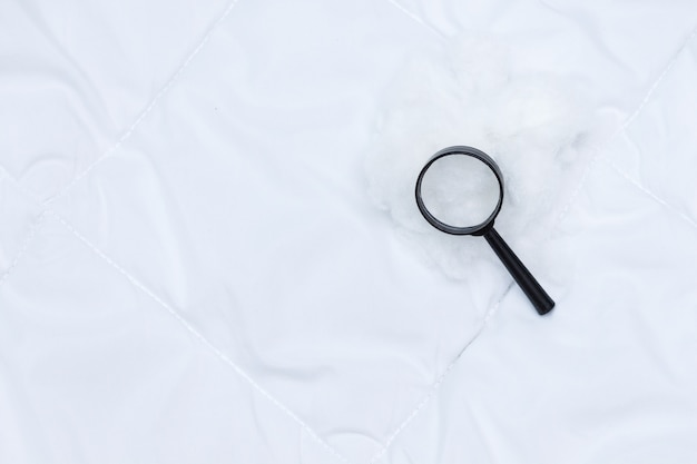 A black magnifier lies on white blanket. detecting bed bugs in bedroom.