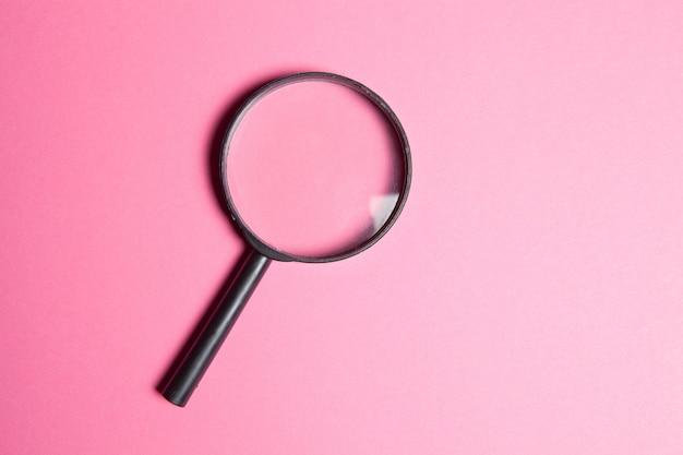 분홍색 배경에 검은 돋보기. 검색 개념