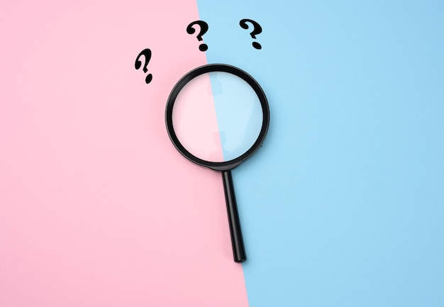 ピンクブルーの表面に黒い拡大鏡と疑問符。不確実性の概念と解決策、疑問、フラットレイの探求
