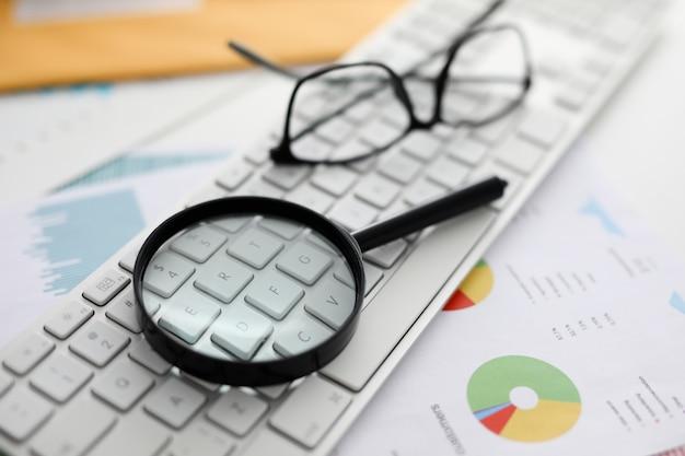 Black magnifying glass lies on white laptop keyboard closeup