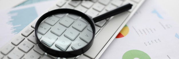 Black magnifying glass lies on white laptop keyboard