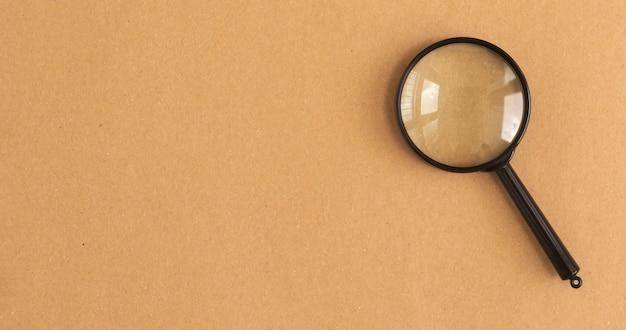 복사 공간 공예 갈색 배경 위에 검은 돋보기. 검색 도구 개념.