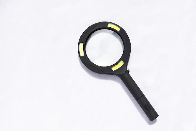 A black magnifying glass with light isolated on white background.