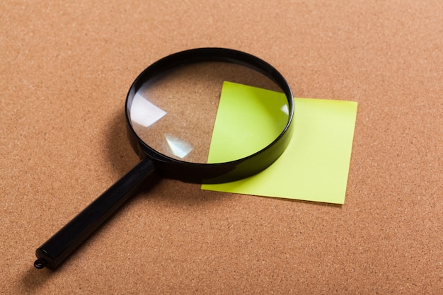 Black magnifying glass, yellow sticky blank notes