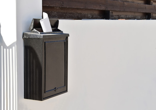 Black mailbox with a letter in the sun