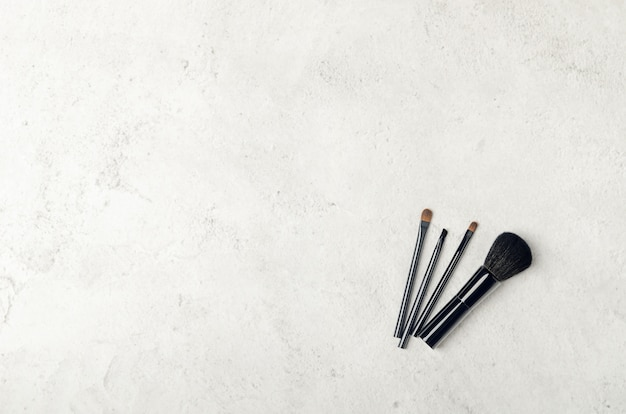 Black makeup brushes on a light stone background