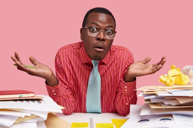 Черный взрослый мужчина пожимает плечами и смотрит с апатией, носит строгую рубашку и синий галстук, не может принять решение