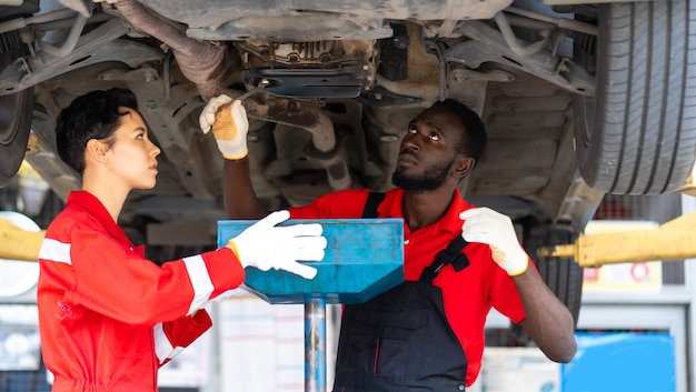 Black male and female trainee mechanics working underneath car together car maintenance and auto service garage.