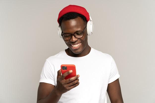 흑인 남성은 스마트폰 스튜디오 촬영에서 소셜 미디어를 사용하여 무선 헤드폰으로 음악을 듣습니다.