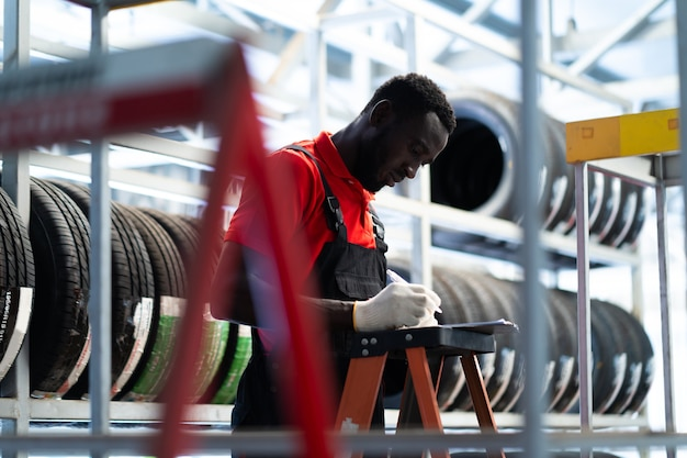 흑인 남성 정비사는 타이어 가게에서 자동차 타이어를 선택합니다. 자동차 수리 차고에서 일하는 전문 정비사.