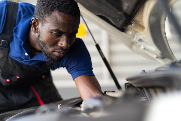 흑인 남성 정비사가 차고에서 차를 수리합니다. 자동차 정비 및 자동 서비스 차고 개념입니다.