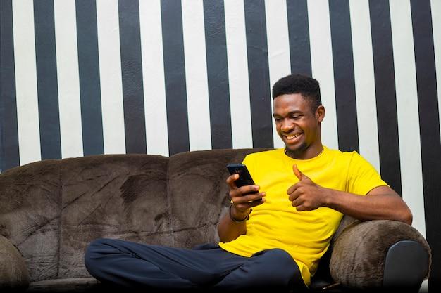 휴대 전화로 인터넷을 확인하는 흑인 남성 밀레니엄 학생