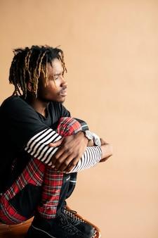 ベージュの壁でポーズをとる黒人男性モデル
