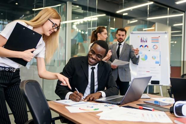 Черный мужской менеджер офиса подписывая финансовые документы для секретарши в его офисе с сотрудниками на предпосылке.