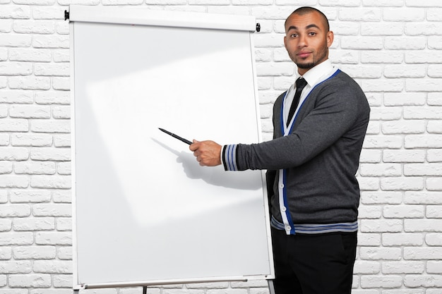 Black male  pointing to  whiteboard