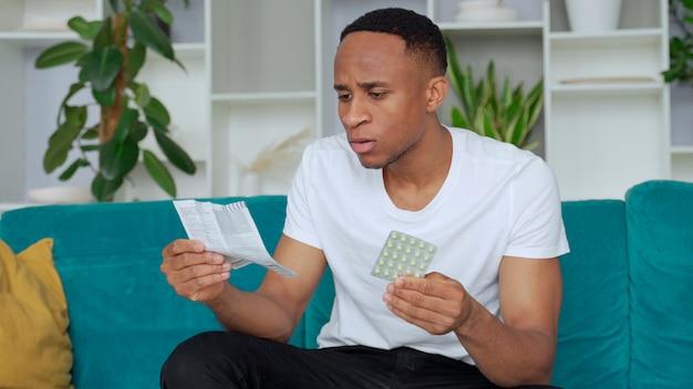 Один черный мужчина сидит на диване, больной и читает инструкции, как принимать концентрированные таблетки