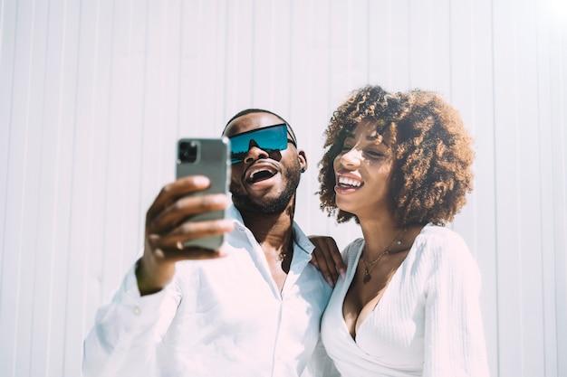 Черный мужчина и афро женщина, делая автопортрет с помощью смартфона.
