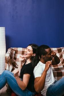 흑인과 백인 여자는 소파에 집에서 이어폰으로 음악을들을 즐길 수