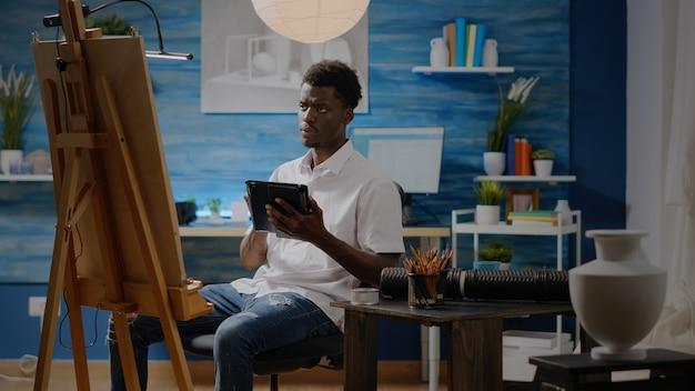 Artista uomo di colore con tavoletta digitale in studio officina