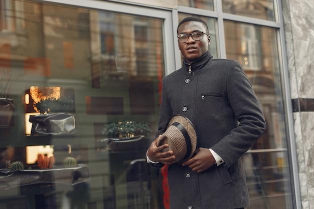 Black man in a black coat in a autumn city