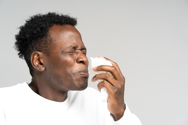 Black man blowing nose and sneeze into tissue or napkin has allergy first symptoms of cold and flu